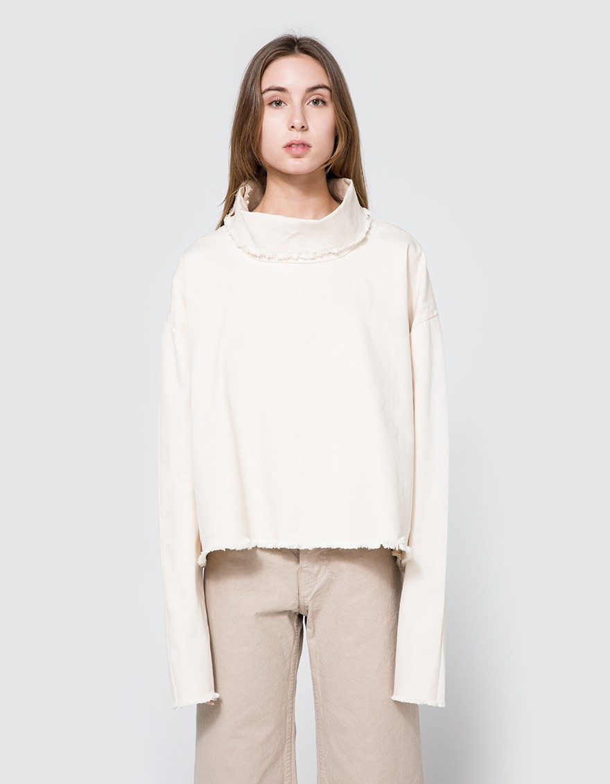 ASHLEY ROWE Turtleneck in Cream  Denim turtleneck from Ashley Rowe in Cream. Turtleneck collar. Dropped shoulders. Tapered long sleeves. Frayed edges. Boxy silhouette.