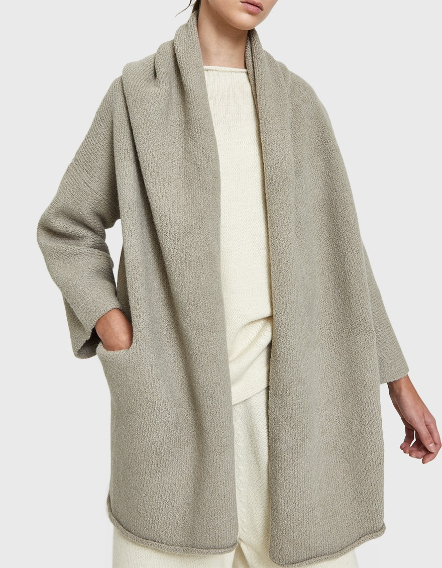 LAUREN MANOOGIAN Capote Coat  Hand-loomed sweater coat from Lauren Manoogian in Cement. Plush rib knit. Seamless hood. Shawl collar. Open front. Dropped shoulders. Front welt pockets. Straight hem.