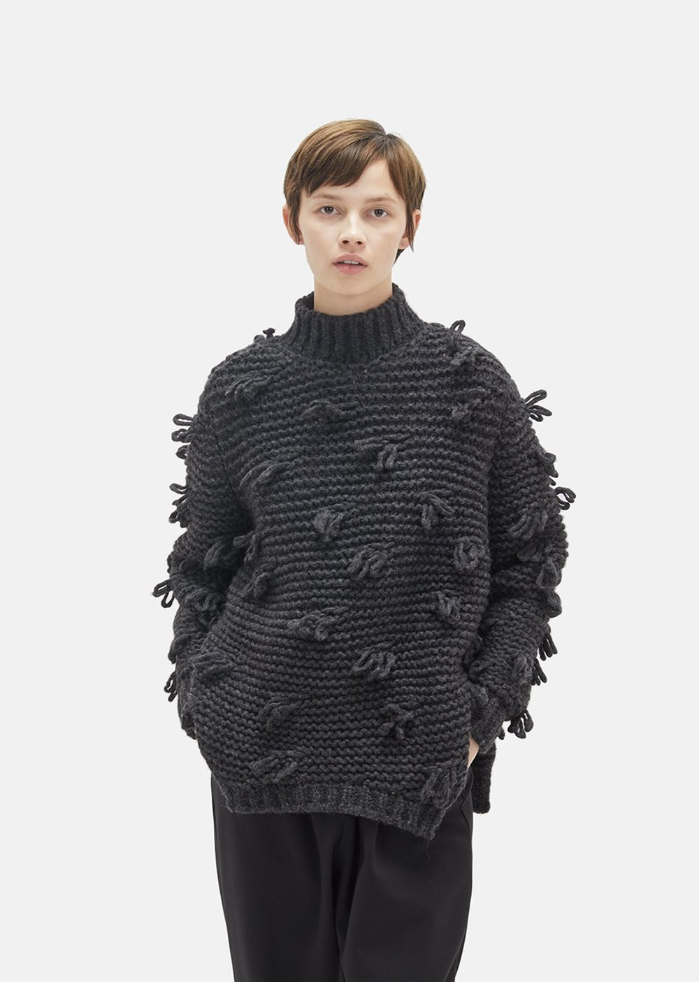 SIMONE ROCHA Tuft Chunky Knit Sweater  Charcoal grey chunky knit turtleneck sweater with allover looped accents. Oversized fit. Ribbed trim on the neck, cuffs, and hem. Open sides with tapered hem. Color: Charcoal. 53% Alpaca, 34% Polyamide, 13% Virgin Wool.