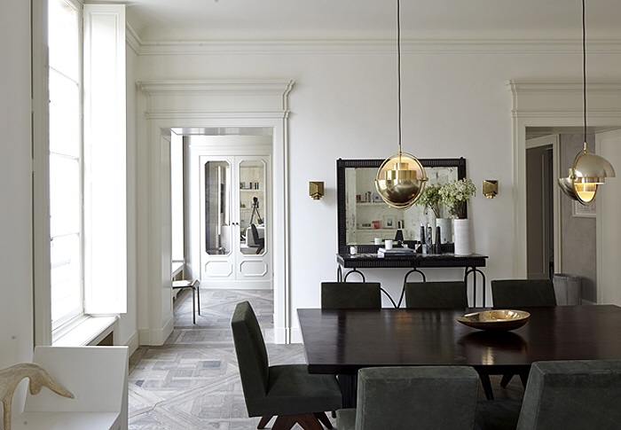 White and grey dinning room with contrasting sharp and dark dinning able and gold pendants