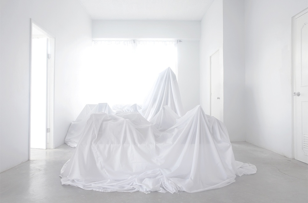 White on white, poised sheet movement amidst white room