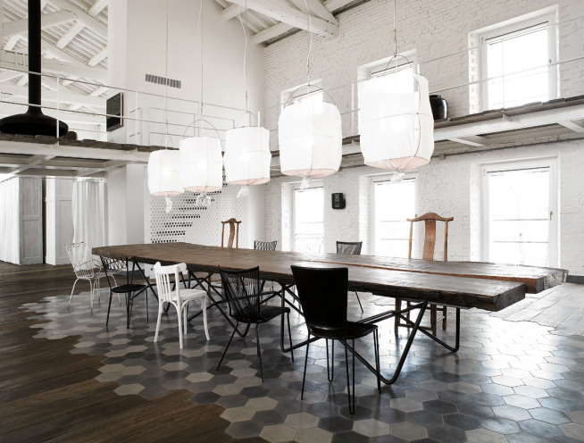 "checkerboard tiling and timber connection, white ""balloon"" fabric chandiliers above a raw timber table and miss-matched chairs. Timber walkway above.."
