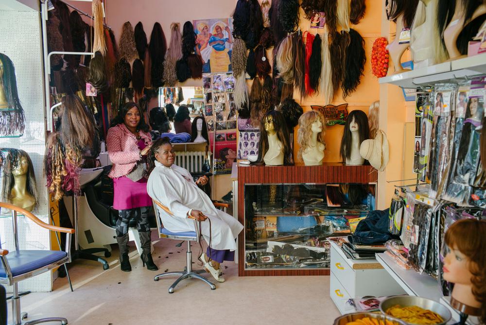Sur les murs du salon, sont accrochées perruques et extensions de toutes les couleurs.
