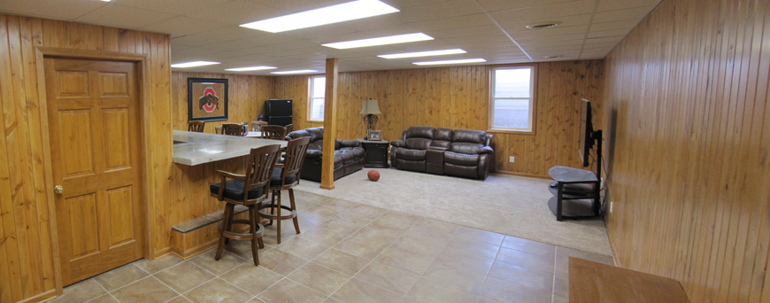 Basement remodel with tiled floors, wood paneled walls and concrete countertops.