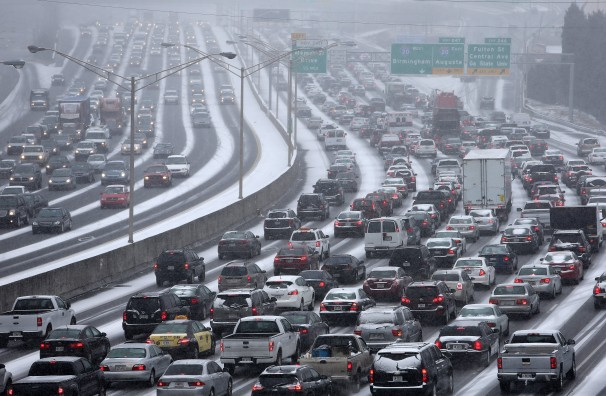 Traffic inches along the connector of Interstate's 75 and 85 as snow blankets Metro Atlanta on Tuesday afternoon, Jan. 28, 2014 as seen from the Pryor Street overpass.  (AP Photo/The Atlanta Journal-Constitution, Ben Gray)