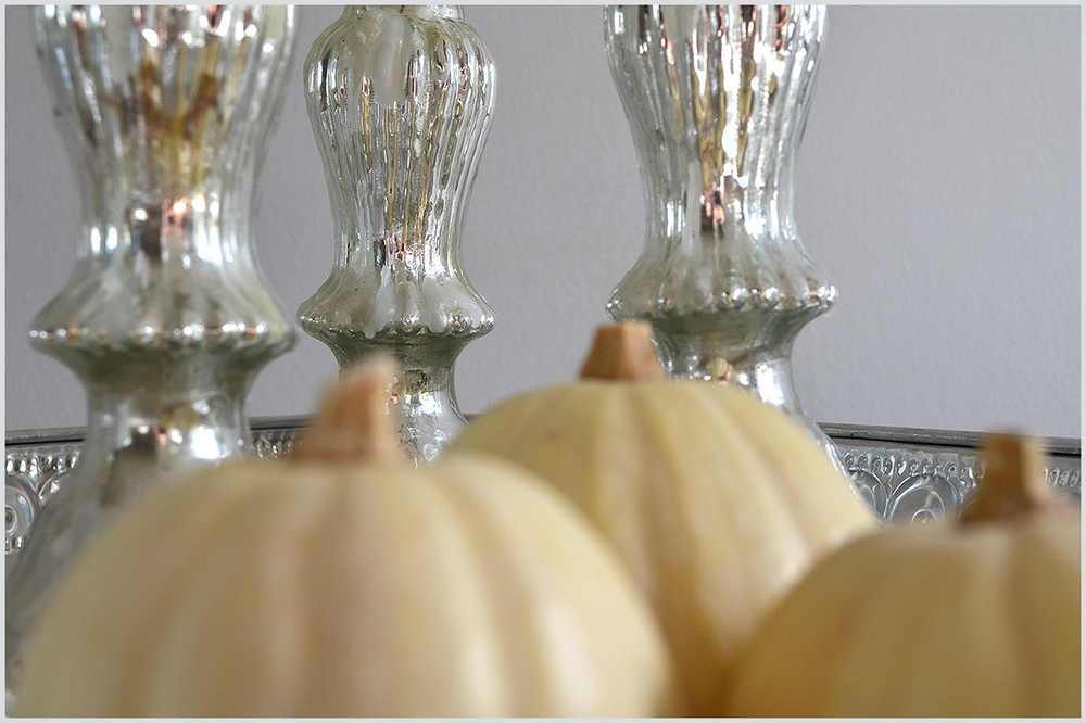 Silver candleholders and white pumpkins