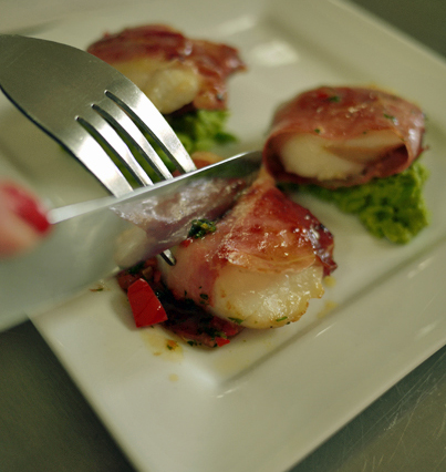 Scallops wrapped in proscuitto on a pea puree