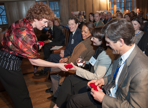 """Eileen Rockefeller Growald presents CASEL's Board Chair Timothy Shriver and President & CEO Karen Neimi with """"Talking Hearts"""" during a donor cultivation event held on March 18, 2014 at the Jane Addams Hull House Resident's Hall on the University of Illinois at Chicago campus."""