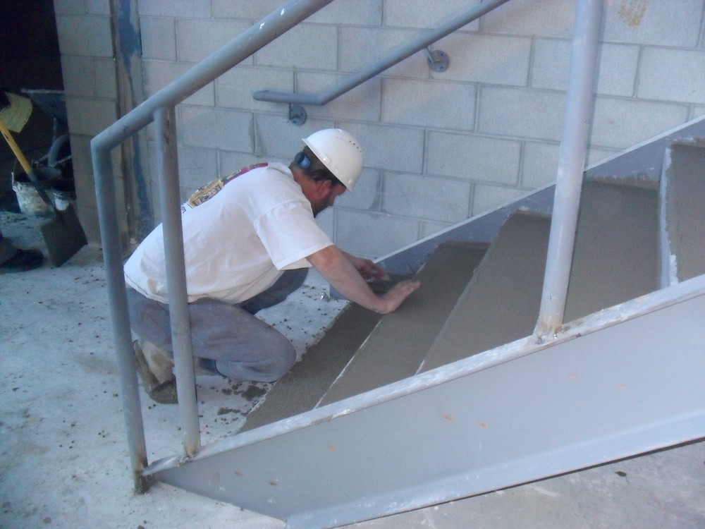 POURED CONCRETE IN THE STAIR TREADS AND TROWELING IT SMOOTH