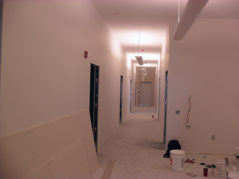 Office hallway with the ceiling lights, wall mounted fire alarm strobe lights and ceiling mounted smoke detectors installed.