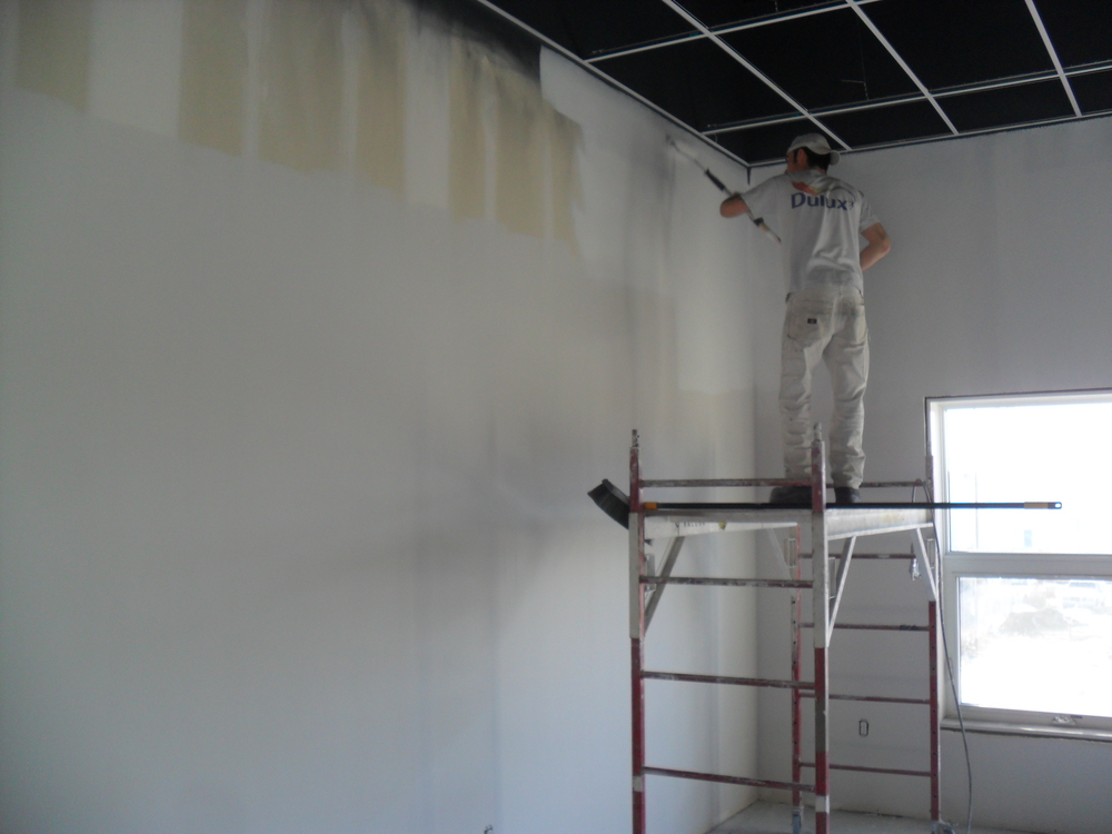 Priming the walls.  First they spray the paint and then they roll it on.