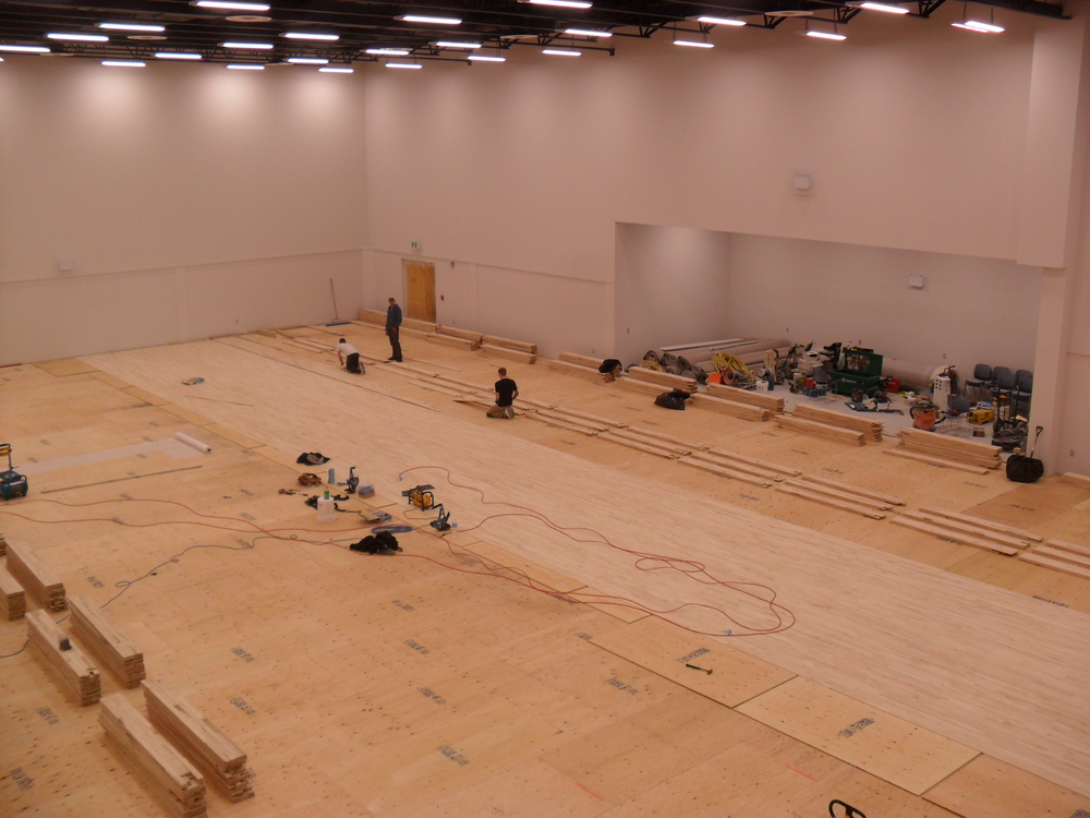 They start laying down the flooring from the centre of the room.