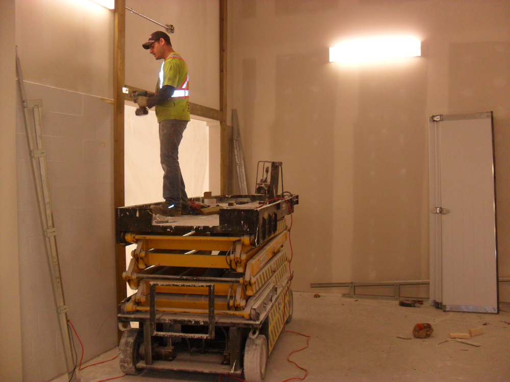 Installing an overhead door at the storage room entry off the sanctuary.