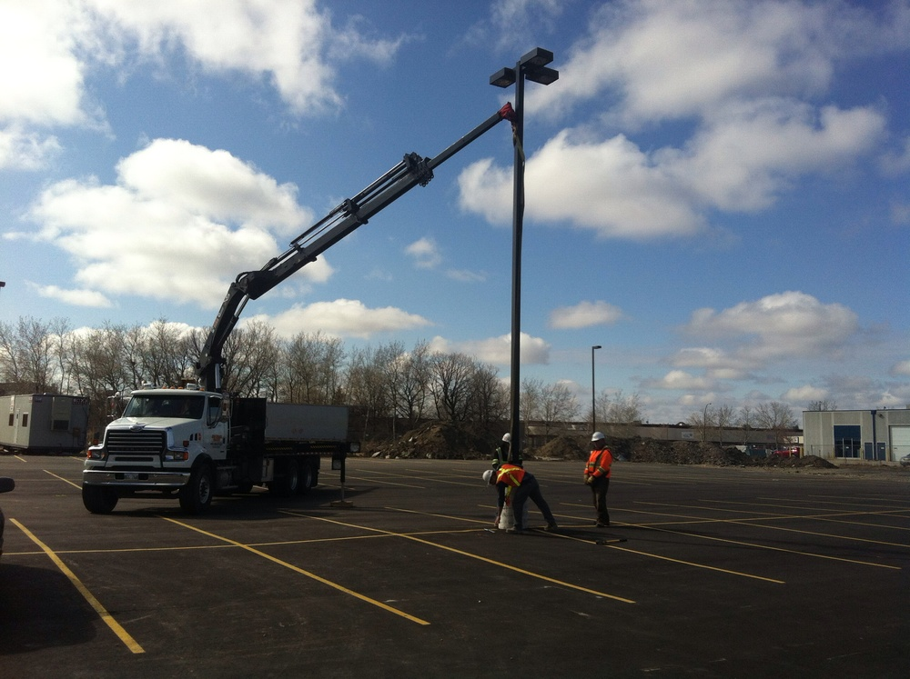 Setting the light pole in place.  Nine lamps were installed and each are 27 feet tall.