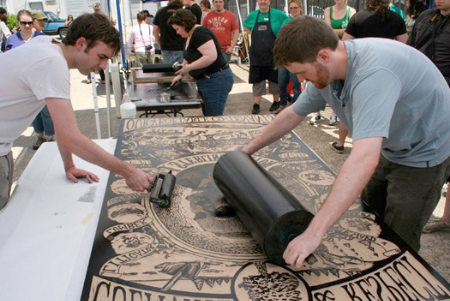 People rolling ink onto giant relief block at a previous Print Big Image from Atlanta Printmaker's Studio