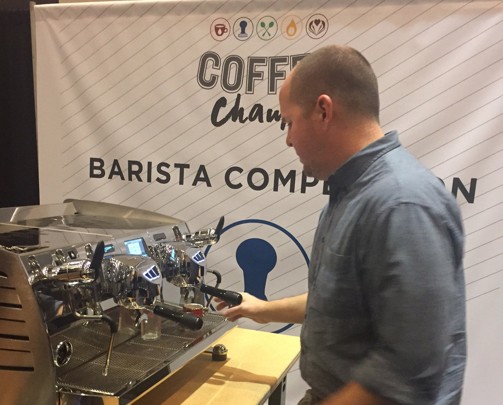 "Jon Lewis, with our friends at Deeper Roots Coffee,  shares his ""Liquid Sunshine"" with the judges on stage. He was also gracious enough to leave some of this delicious Kenya AA from the Kiriani Farmers Cooperative Society with us to serve on our pour-over bar."