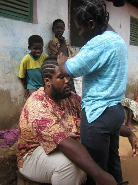 John getting his hair braided in Ghana.