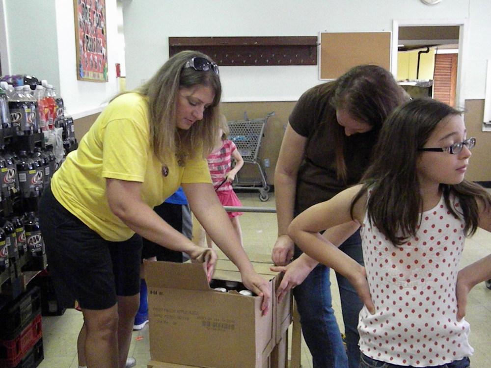 Family of Faith volunteers help unpack food and organize it into groups for easy access.