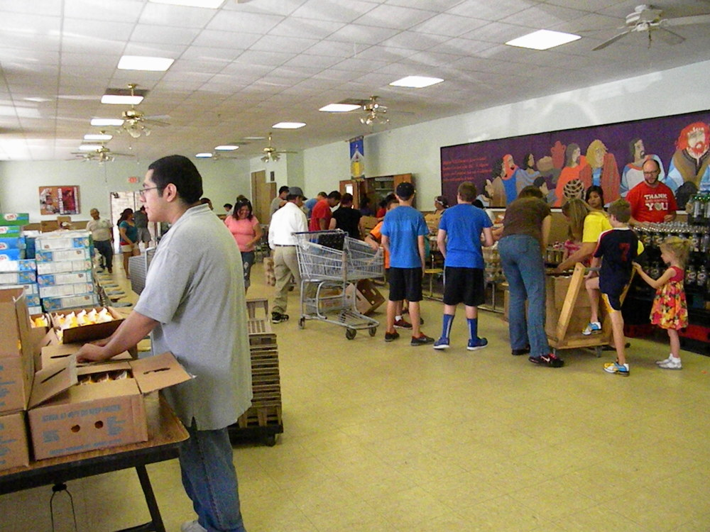 Volunteers at CDG are working hard moving boxes of food into the space and unpacking them.
