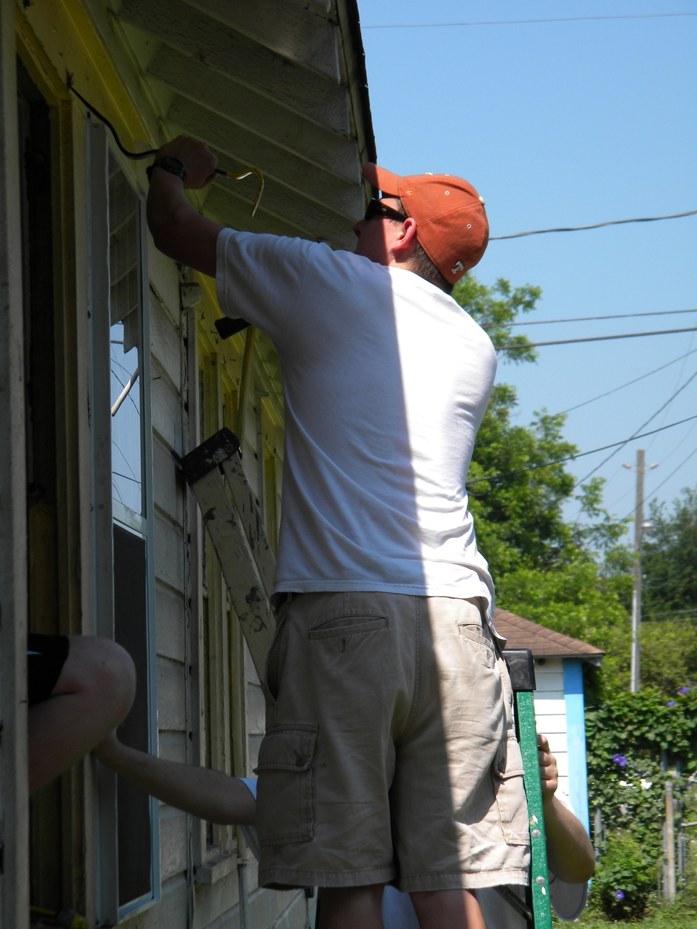 Students work on window frames to install new windows for family.