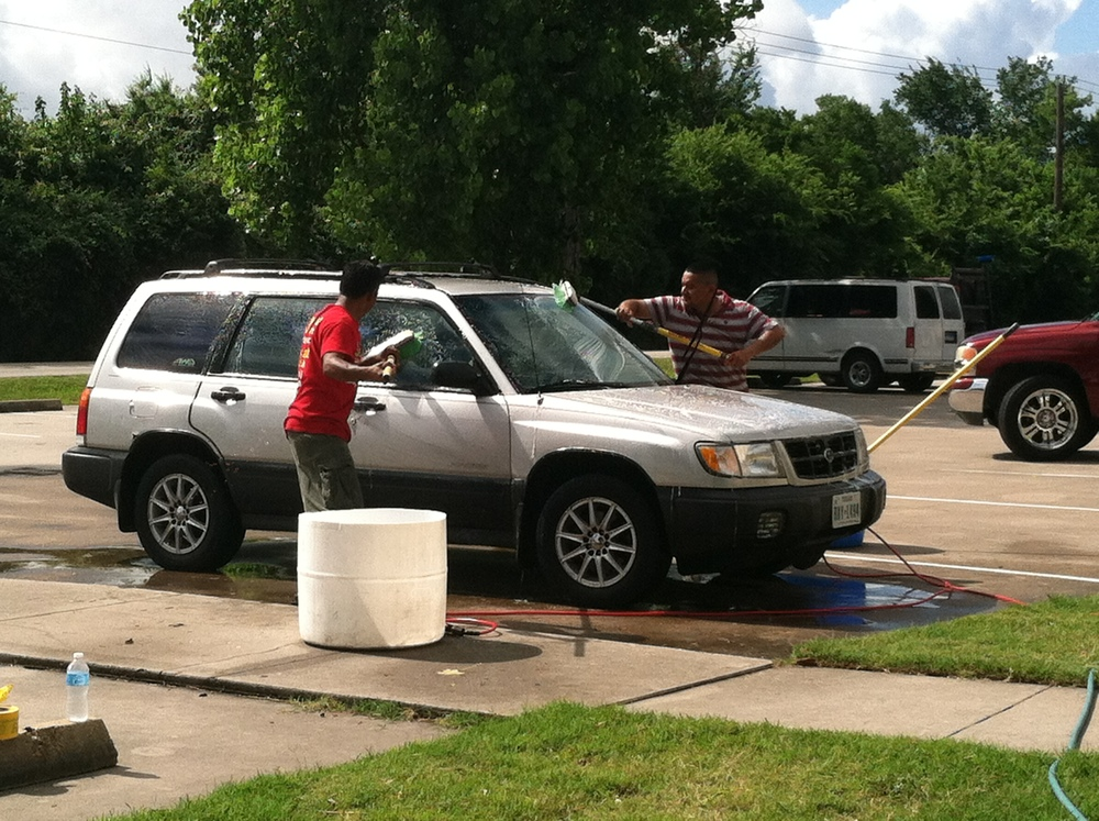 Members washing cars to help raise money for their music ministry.