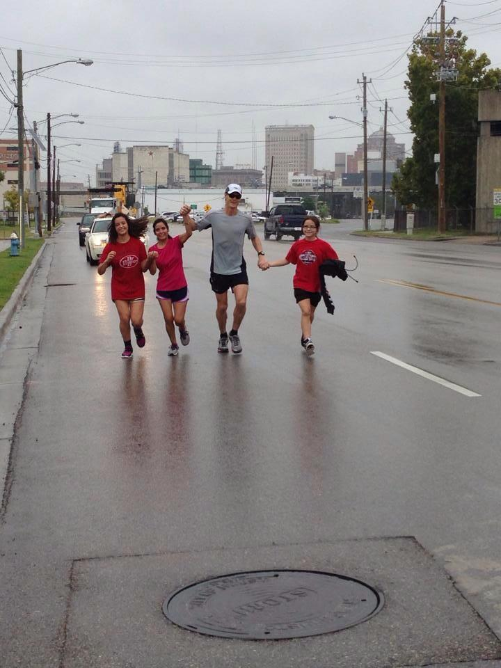 Mark crosses finish line with wife and daughters holding his hands.