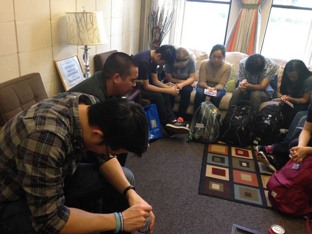 Students pray before going out to share the Gospel with University Students.