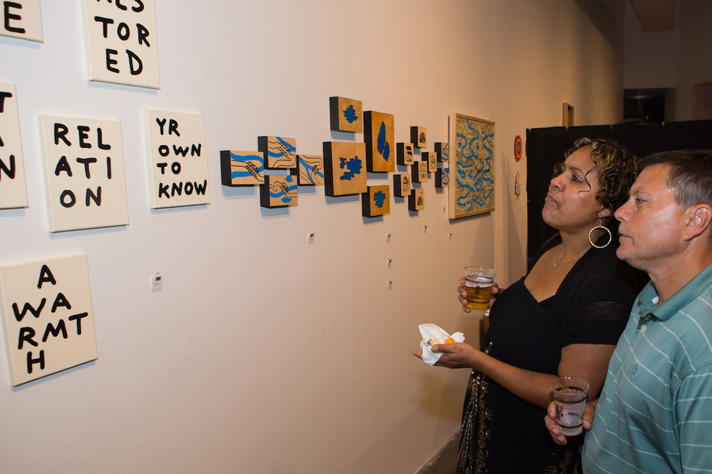 Attendees admire works by Pittsburgh artist, Seth LeDonne.