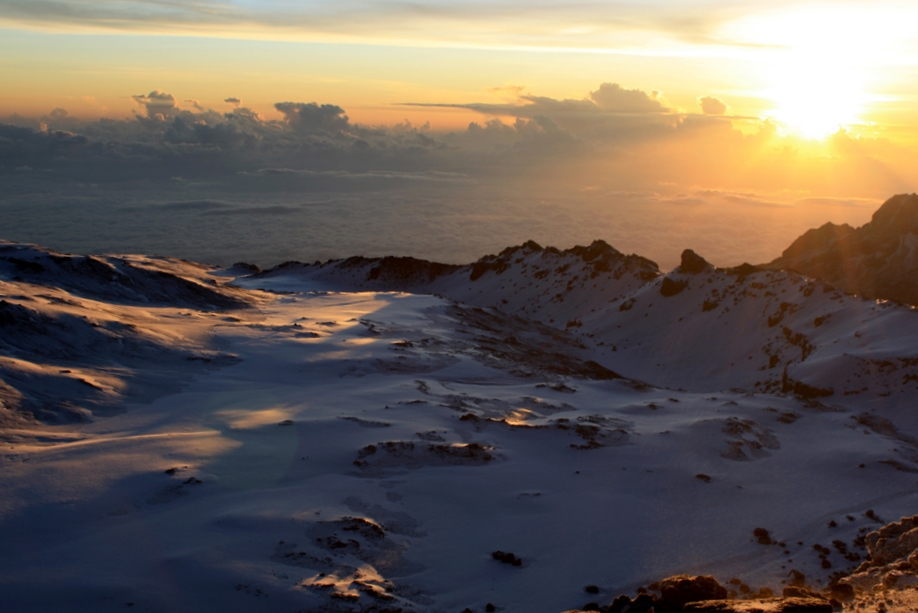 View from Uhuru peak at sunrise! Here, the snow capped summit of Kilimanjaro stands at 19,341 feet, making it the tallest peak in Africa, and the highest free standing mountain in the world. .