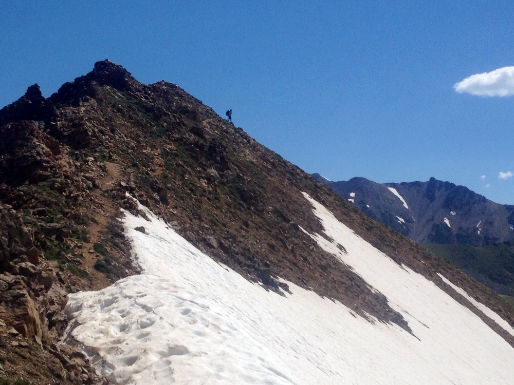 Analog climbs a peak along the Gore Range.