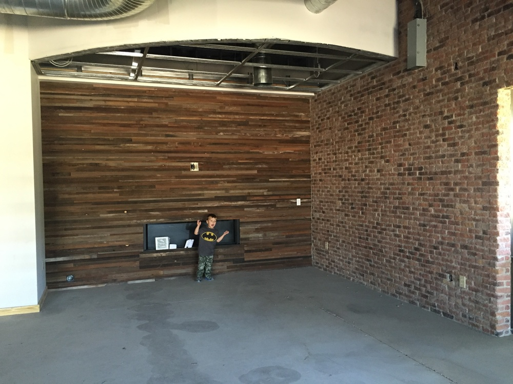 Here is Tribb posing in front of the reclaimed wood fireplace wall.