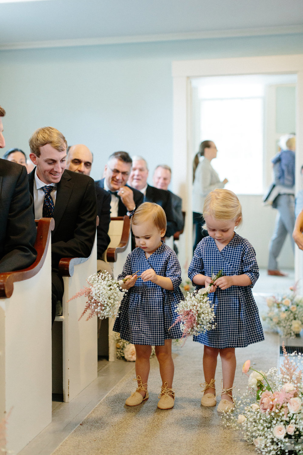 - One of my favorite photos from our ceremony. Two of our five precious flower girls, Charley Kettler and Stella Blair making their way down the aisle at their own pace. They looked so sweet in our custom Raffia Lace Ups, and custom Smiling Button dresses.