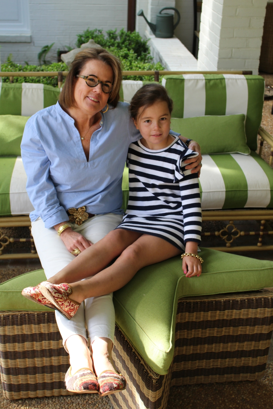 Coco sitting with her neighbor, Susan, outside on the patio wearing our Kilim shoes.