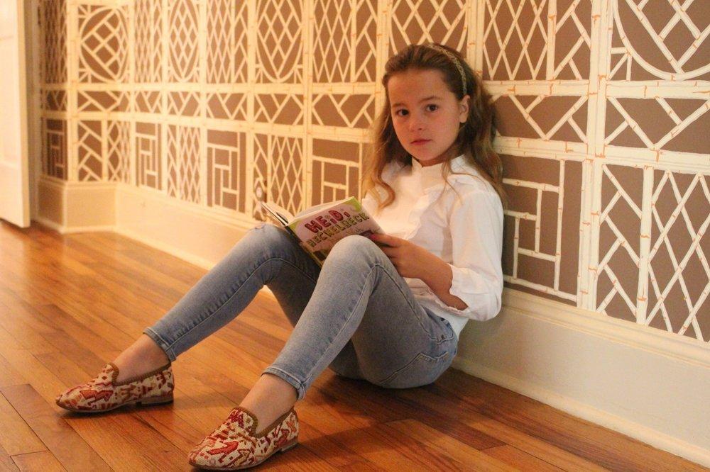 Coco sitting inside reading while wearing our Children's Kilim shoes.