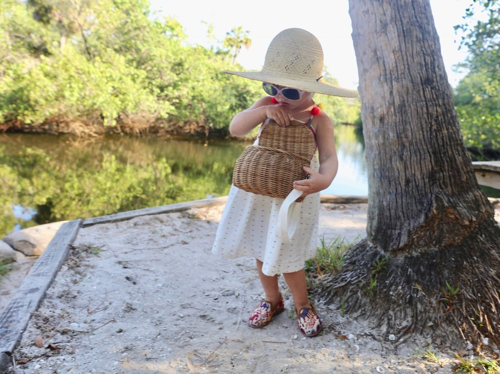 Madeline wearing our Children's Kilim Loafers while holding a basket outside next to a tree.