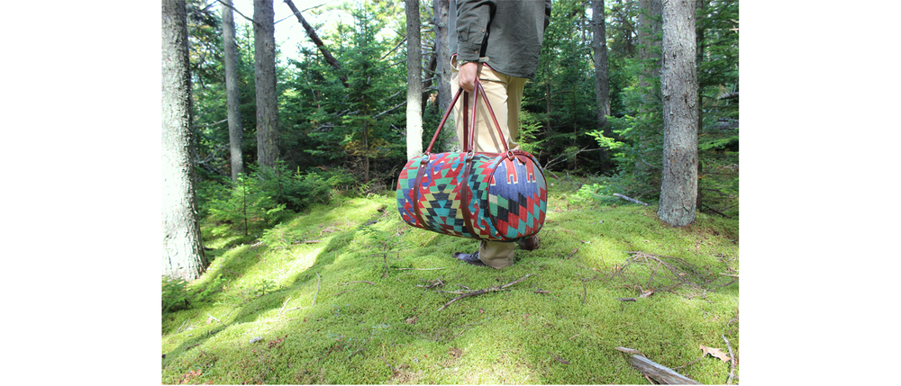 Brian holding our Kilim bag for men in the mossy forest.