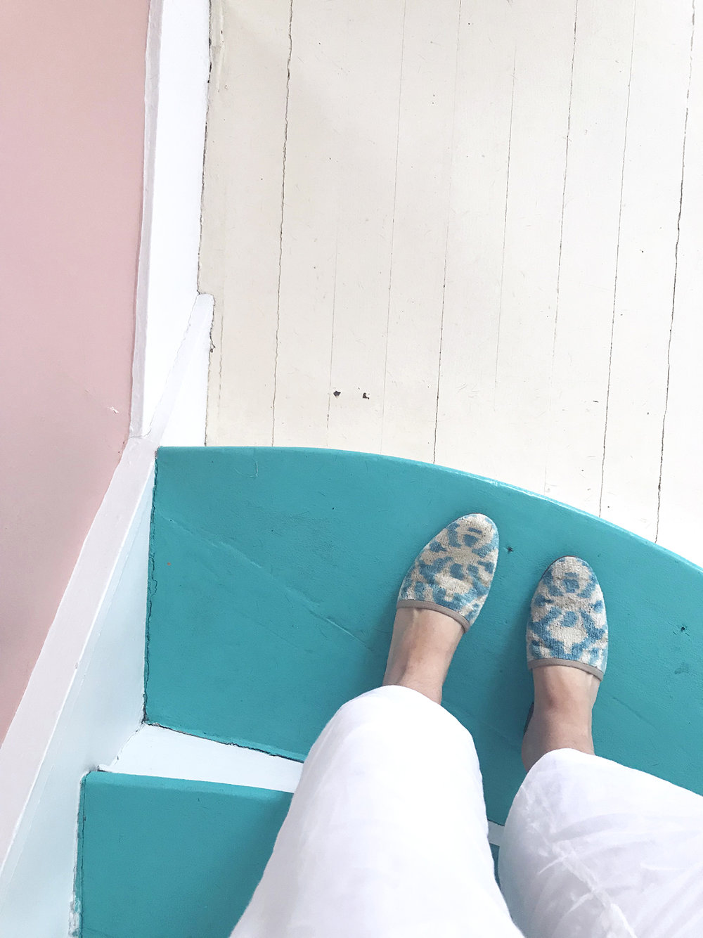 Carson velvet slides or velvet mules on the teal stairs in Provincetown, MA.