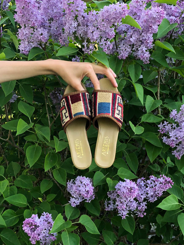 Our Kilim Sandals in front of a lilac bush in Friendship, Maine.