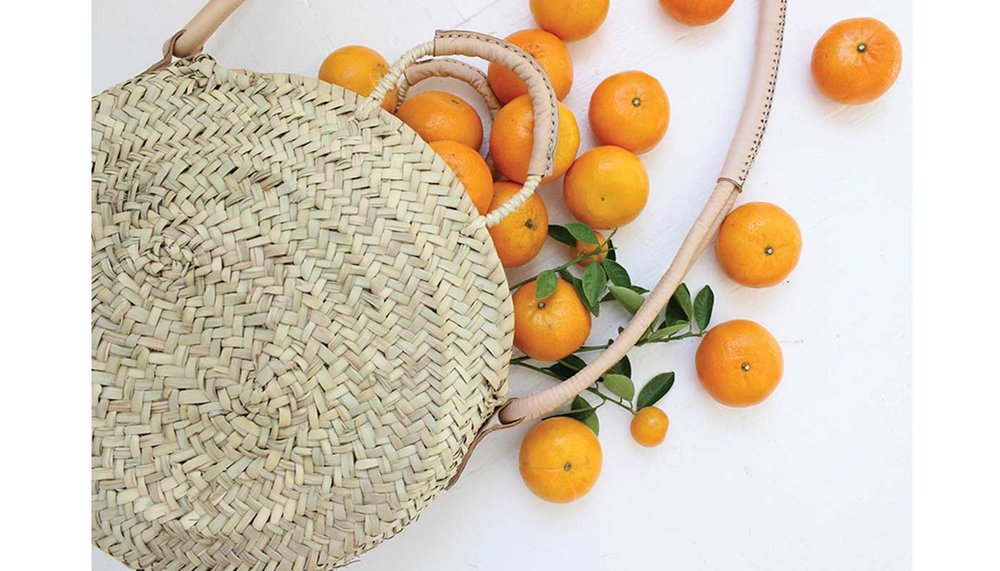 Artemis Design Co. Raffia Bag filled with oranges.