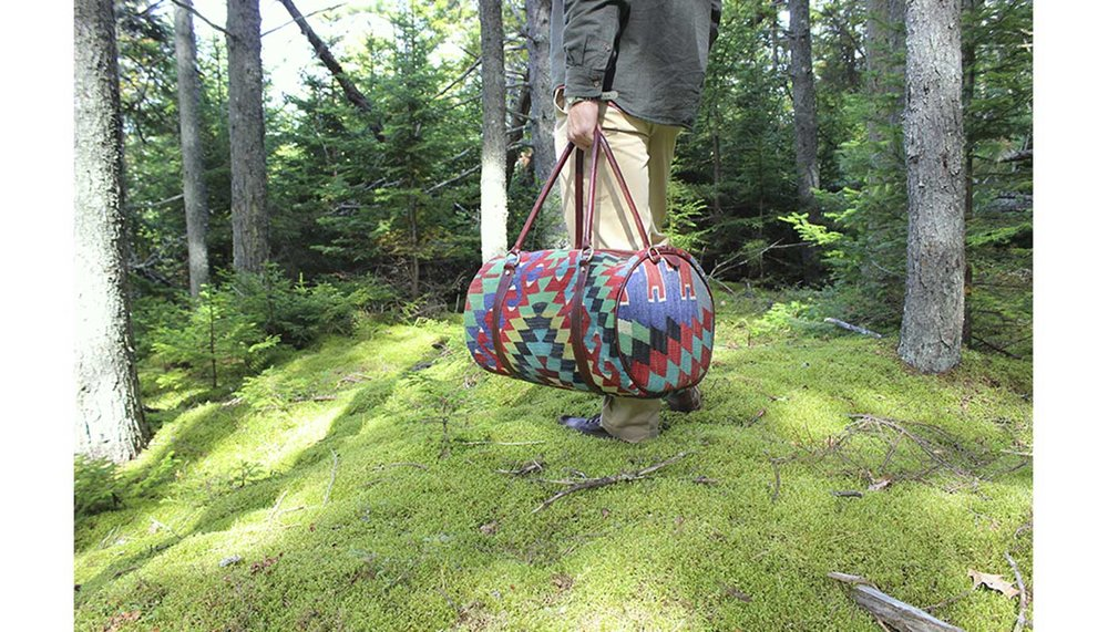 Artemis Design Co. Travel Duffle Kilim Bag held by Brian in the mossy forest.