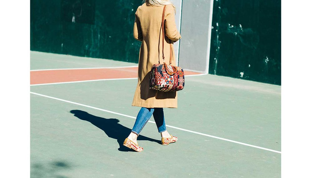Artemis Design Co. Baby Duffle Kilim Bag on model Tory, she is walking across a tennis court in the South End of Boston.