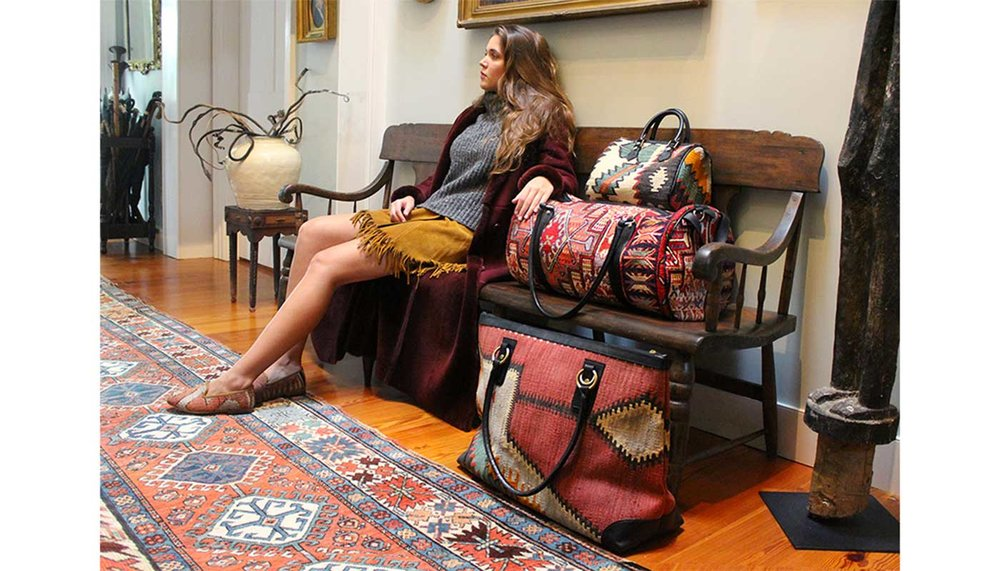 Artemis Design Co. Weekender Kilim Bag sitting on the floor next to a carpet, photo taken in Westport, CT, Model: Yasmine.