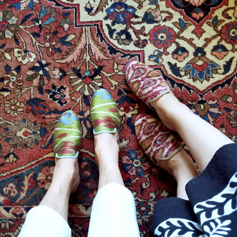 McNeill and her mom wearing custom silk slippers and velvet slippers on a Kilim carpet in McNeill's parent's home.