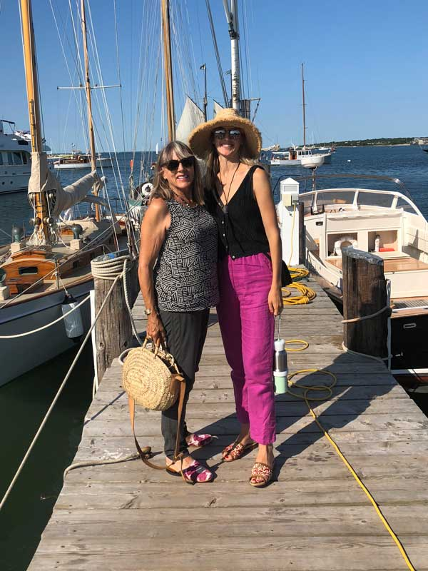 Milicent and her mother stand wearing Artemis shoes on a dock in Maine.