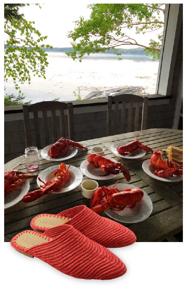 A pair of red Artemis raffia Babouches sits edited over a photo of a dinner table with lobster in Maine.
