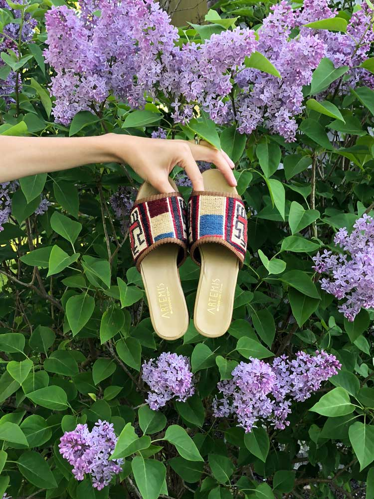 A model holds a pair of Artemis kilim sandals in front of a flower bush in Maine.