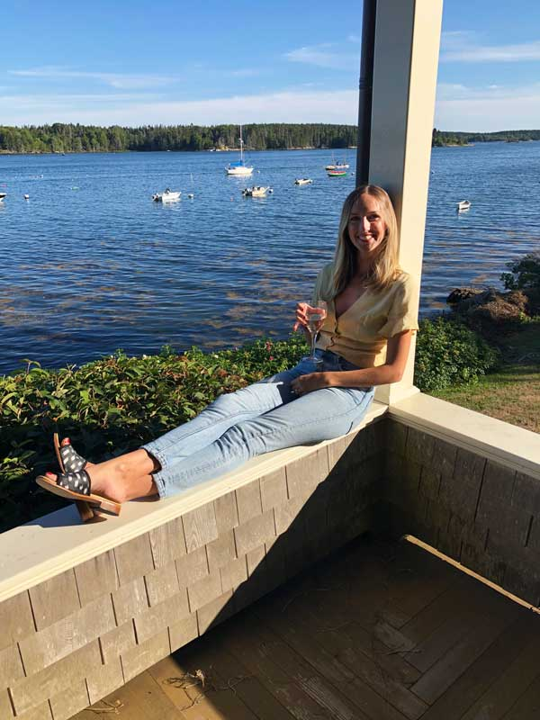 Milicent sits on a balcony in Maine with her Artemis silk sandals.