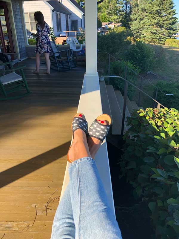 A downwards facing photograph of Artemis silk sandals modeled in Maine.