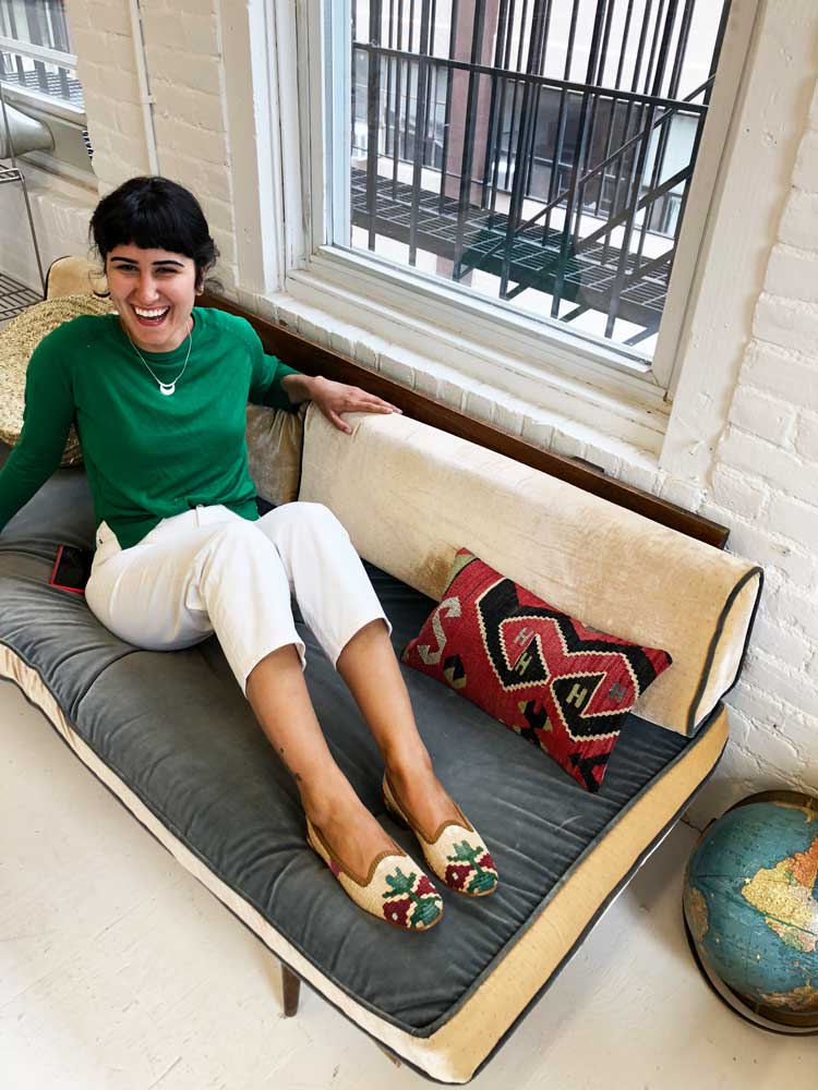 A customer poses on a couch wearing Artemis classic kilim loafers.