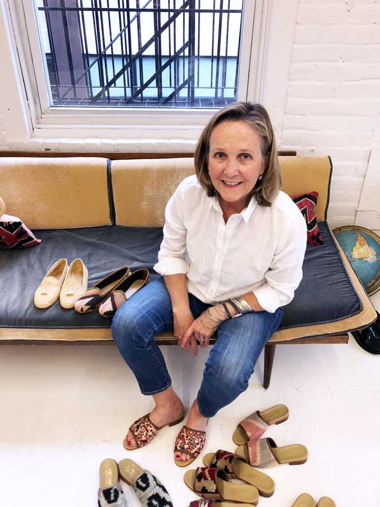 A customer sits on a couch wearing Artemis kilim sandals.